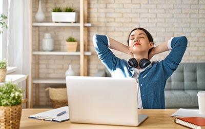 Frau lehnt sich bei Arbeit entspannt zurück