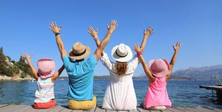 glückliche Familie streckt Arme in den blauen Himmel