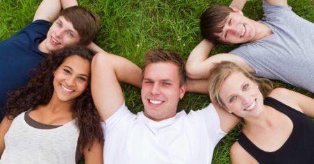 Jungendliche liegen zusammen auf einer Wiese