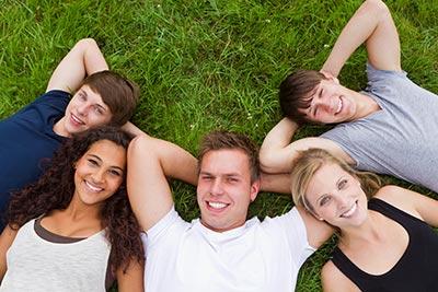 Schüler liegen zusammen auf einer Wiese